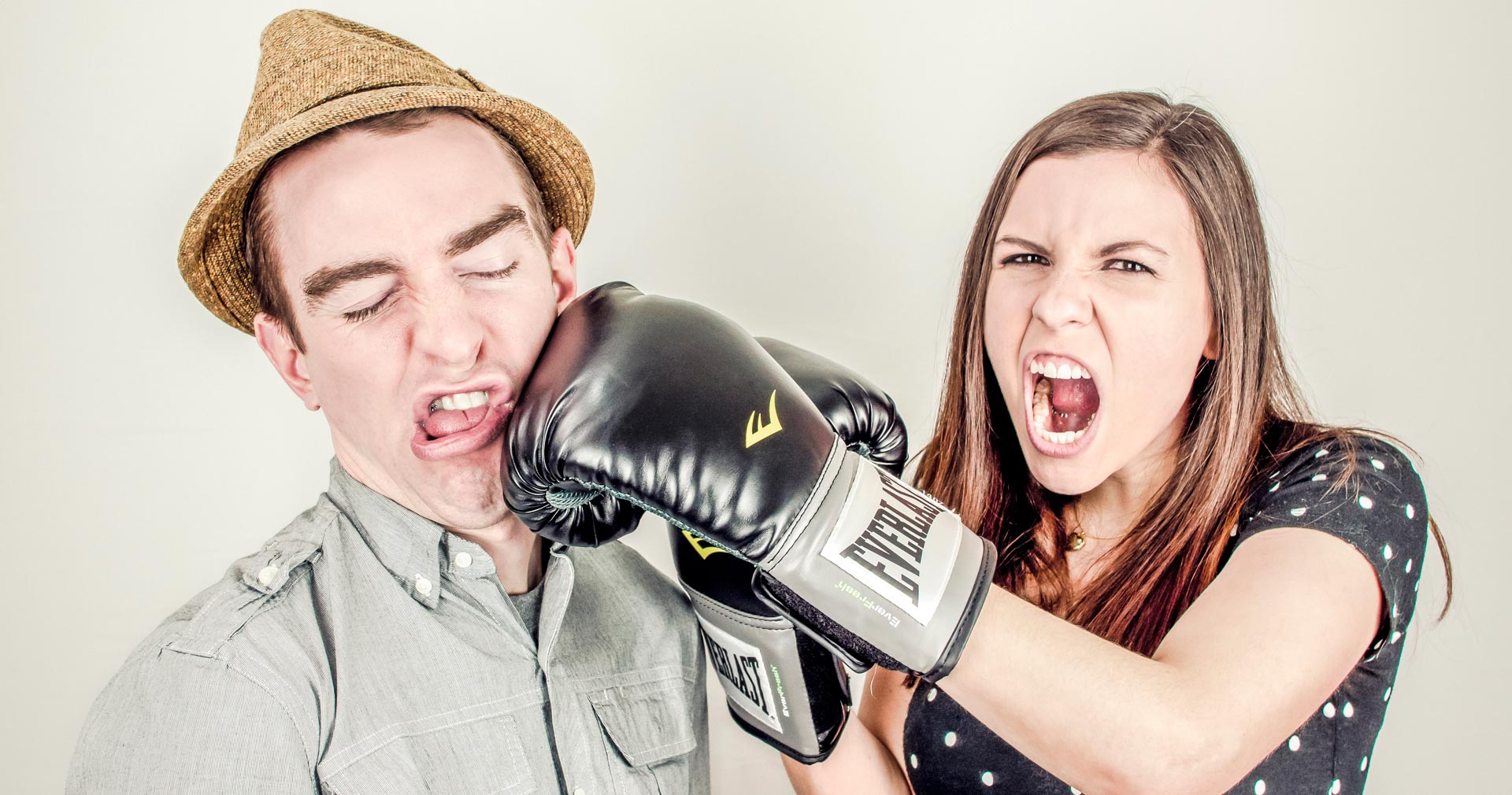 Image of a girl wearing boxing gloves punching a guy in a hat
