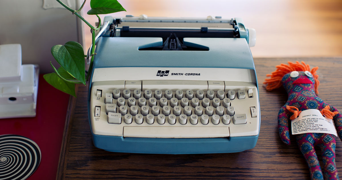 image of typewriter with a voodoo doll