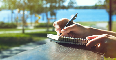 A person writing outdoors with lake in the background
