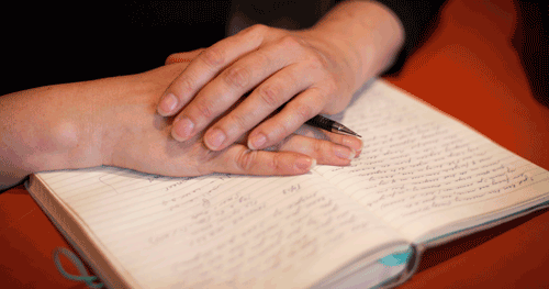woman's hands with notebook and pen