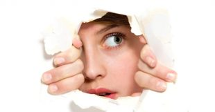 Image of a woman peering through a hole in a piece of paper