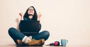 Woman with laptop raising her fists in success