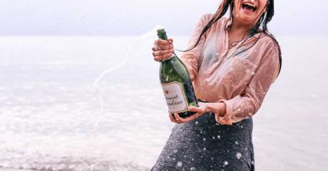 Woman with a spewing bottle of bubbly, clearly feeling celebratory
