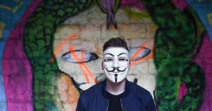 Guy in a mask in front of street art painting of guy in a mask
