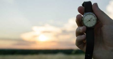Photo: Man holding watch looking at the sunset - clearly running out of time to publish his flash fiction piece