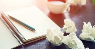 Image: notebook with paper wadded in frustration, clearly a case of writer's block