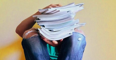 Person holding a stack of journals