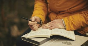 Photo of a man journaling to become a better writer