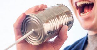Photo of a man speaking into a tin can intending to suggest someone who needs our top tips for writing dialogue that sounds natural