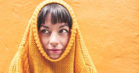 a girl with a sweater over her head clearly worried about submitting her writing to a literary journal for the first time