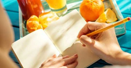 Summer courses in Amsterdam [Photo: woman writing with oranges]